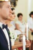 Η νύφη φαίνεται σοβαρά κρατώντας ένα κερί στα όπλα της κατά τη διάρκεια του CE Στοκ φωτογραφίες με δικαίωμα ελεύθερης χρήσης