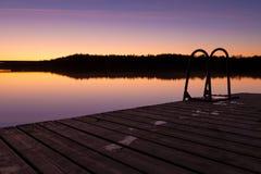 Η νύχτα κολυμπά την αποβάθρα και την ήρεμη λίμνη στο λυκόφως Στοκ εικόνες με δικαίωμα ελεύθερης χρήσης