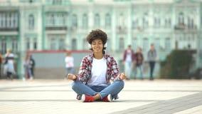 Η ξένοιαστη νέα θηλυκή συνεδρίαση στο λωτό θέτει και ακούοντας τη μουσική στα ακουστικά απόθεμα βίντεο