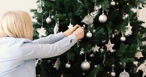 Η ξανθή γυναίκα βγάζει το χριστουγεννιάτικο δέντρο παιχνιδιών πάγου απόθεμα βίντεο