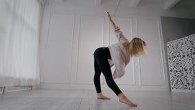 Η ξανθή γυναίκα είναι σύγχρονη απόδοση χορού στην αίθουσα κατάρτισης, στην ημέρα μόνη, τα πόδια αύξησης επάνω και περιστροφή απόθεμα βίντεο
