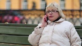 Η ξανθή γυναίκα κάθεται στον πάγκο και μιλά στο τηλέφωνο απόθεμα βίντεο