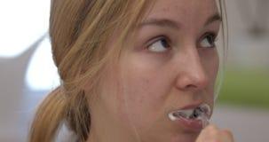 Η ξανθή γυναίκα καθαρίζει τα δόντια απόθεμα βίντεο