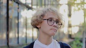 Η ξανθή γυναίκα με τα γυαλιά εξετάζει δυστυχώς τη κάμερα φιλμ μικρού μήκους
