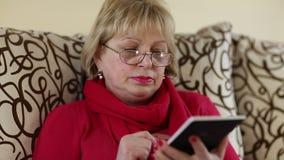 Η ξανθή γυναίκα με τα κόκκινα καρφιά και το κόκκινο κραγιόν κάθεται στον καναπέ με την ηλεκτρονική συσκευή απόθεμα βίντεο