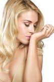 Η ξανθή γυναίκα ομορφιάς μυρίζει το άρωμά του στο λευκό Στοκ Εικόνες