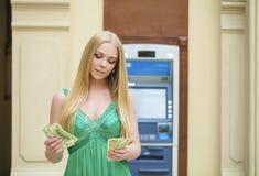 Η ξανθή γυναίκα σε ένα πράσινο φόρεμα κρατά τα δολάρια μετρητών Στοκ φωτογραφία με δικαίωμα ελεύθερης χρήσης