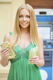 Η ξανθή γυναίκα σε ένα πράσινο φόρεμα κρατά τα δολάρια μετρητών Στοκ Φωτογραφία