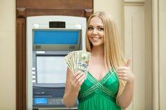 Η ξανθή γυναίκα σε ένα πράσινο φόρεμα κρατά τα δολάρια μετρητών Στοκ Εικόνα