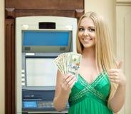 Η ξανθή γυναίκα σε ένα πράσινο φόρεμα κρατά τα δολάρια μετρητών Στοκ εικόνα με δικαίωμα ελεύθερης χρήσης