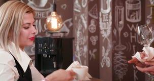 Η ξανθή θηλυκή σερβιτόρα laughts και απολαμβάνει coffe μετά από την εργασία απόθεμα βίντεο