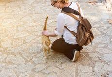 Η ξανθή ικεσία γυναικών επάνω η petting γάτα οδών στοκ φωτογραφίες με δικαίωμα ελεύθερης χρήσης