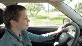 Η ξανθή κοντή γυναίκα τρίχας οδηγεί το αυτοκίνητο στις οδούς πόλεων απόθεμα βίντεο