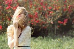 Η ξανθή νέα γυναίκα καλλιεργεί την άνοιξη Κορίτσι με πετάγματος ανθίζοντας φύση χαμόγελου και απόλαυσης τρίχας την καλή Στοκ εικόνες με δικαίωμα ελεύθερης χρήσης