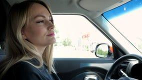 Η ξανθή νέα γυναίκα οδηγεί ένα αυτοκίνητο στην πόλη απόθεμα βίντεο