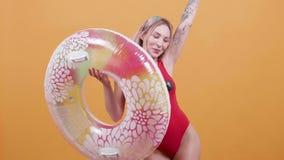 Η ξανθή νέα γυναίκα στις swimwear συλλήψεις κολυμπά το δαχτυλίδι και τους χορούς απόθεμα βίντεο