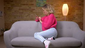Η ξανθή νοικοκυρά στη ρόδινη συνεδρίαση πουλόβερ στο σχεδιάγραμμα στον καναπέ που κάνει σερφ στο smartphone χαμογελά στη κάμερα σ απόθεμα βίντεο