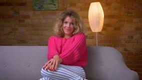 Η ξανθή νοικοκυρά στο ρόδινο πουλόβερ στον καναπέ που προσέχει τη TV παρουσιάζει τρυφερές συγκινήσεις και αγκαλιάζεται στο άνετο  φιλμ μικρού μήκους