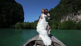 η ξανθή νύφη θέτει και αγκράφες για να καλλωπίσει τη στάση στη βάρκα longtail απόθεμα βίντεο