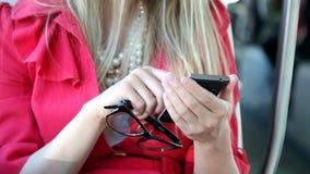 Η ξανθή συνεδρίαση κοριτσιών στο τραμ, κλείνει επάνω σε κινητό, τηλέφωνο, κύτταρο απόθεμα βίντεο