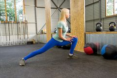 Η ξανθή όμορφη γυναίκα κάνει το τέντωμα από τα μαστίγια που αυξάνουν το πόδι της στοκ εικόνες