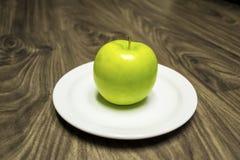 Η ξινή πράσινη Apple που κάθεται στο άσπρο πιάτο Στοκ εικόνα με δικαίωμα ελεύθερης χρήσης