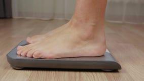 Η ξυπόλυτη γυναίκα που ελέγχει το βάρος στην κλίμακα, μετακινείται τον πυροβολισμό φιλμ μικρού μήκους