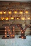 Η ξύλινη Νέα Υόρκη επιστολών με τα φω'τα βολβών στο ξύλινο υπόβαθρο τοίχων Ιδέα σοφιτών η έννοια Χριστουγέννων απομόνωσε το νέο ά στοκ εικόνες