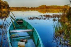 Η ξύλινη βάρκα έδεσε στη λίμνη στην ξηρά στη ρωσική αγροτική φύση Στοκ εικόνες με δικαίωμα ελεύθερης χρήσης