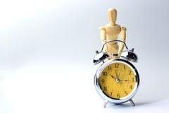 Η ξύλινη κούκλα αριθμού προσπαθεί να ενεργοποιήσει το εκλεκτής ποιότητας ρολόι στο λευκό για το καπνιστό πικάντικο λουκάνικο Στοκ Φωτογραφία