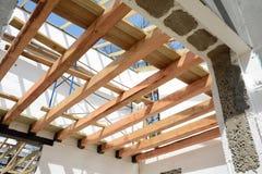 Η ξύλινη δομή του κτηρίου Εγκατάσταση των ξύλινων ακτίνων στην κατασκευή το σύστημα ζευκτόντων στεγών του σπιτιού Στοκ Φωτογραφία