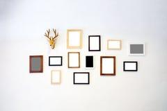 Η ξύλινη φωτογραφία πλαισίων διακοσμεί στον άσπρο τοίχο Στοκ Εικόνα
