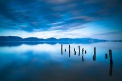 Η ξύλινος αποβάθρα ή ο λιμενοβραχίονας παραμένει σε ένα μπλε ηλιοβασίλεμα και έναν ουρανό λιμνών refle Στοκ Φωτογραφία