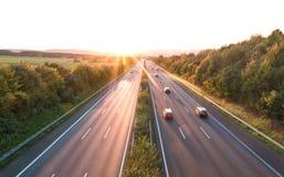 Η οδική κυκλοφορία σε έναν αυτοκινητόδρομο στο ηλιοβασίλεμα στοκ φωτογραφία