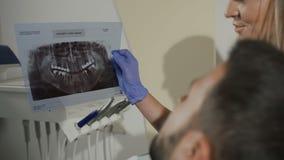 Η οδοντίατρος-γυναίκα παρουσιάζει στον ασθενή μια ακτίνα X για την περαιτέρω θεραπεία των δοντιών οδοντιατρική Ο οδοντίατρος παρο απόθεμα βίντεο