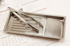 Η οδοντική λαβίδα βρίσκεται στον ιατρικό δίσκο Στοκ Φωτογραφίες