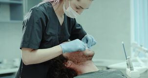 Η οδοντική νέα υπομονετική συνεδρίαση δωματίων κλινικών στα dentis προεδρεύει και ο οδοντίατρος βάζει τη στοματική φρουρά στο στό απόθεμα βίντεο