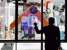 Η οθόνη αφής μηχανικών ελέγχει την παραγωγή των ρομπότ βιομηχανίας κατασκευής μερών εργοστασίων Στοκ Εικόνες