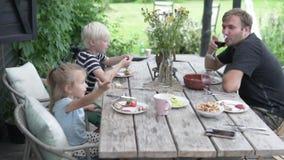 Η οικογένεια έχει το μεσημεριανό γεύμα στη βεράντα στο summe φιλμ μικρού μήκους