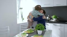 Η οικογένεια αγκαλιάζει, ευτυχής αγκαλιά γονέων με το παιδί στο πρόγευμα στον πίνακα απόθεμα βίντεο