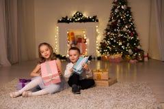 Η οικογένεια αγοριών και κοριτσιών ανοίγει τις νέες γιρλάντες χριστουγεννιάτικων δέντρων φω'των διακοπών έτους δώρων Χριστουγέννω στοκ εικόνα
