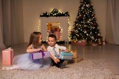 Η οικογένεια αγοριών και κοριτσιών ανοίγει τις νέες γιρλάντες χριστουγεννιάτικων δέντρων φω'των διακοπών έτους δώρων Χριστουγέννω στοκ εικόνες