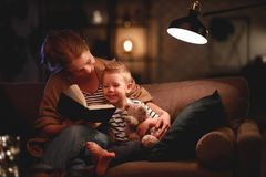 Η οικογένεια ενώπιον της πηγαίνοντας στο κρεβάτι μητέρας διαβάζει στο βιβλίο γιων παιδιών της κοντά σε έναν λαμπτήρα το βράδυ στοκ εικόνα με δικαίωμα ελεύθερης χρήσης
