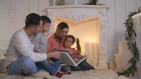 Η οικογένεια διάβασε τη συνεδρίαση βιβλίων στον καναπέ μπροστά από την εστία διακοσμημένο στο Χριστούγεννα εσωτερικό σπιτιών απόθεμα βίντεο