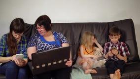 Η οικογένεια κάθεται στον καναπέ και χρησιμοποιεί τις ψηφιακές συσκευές απόθεμα βίντεο