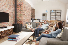 Η οικογένεια κάθεται στον καναπέ στην ανοικτή τηλεόραση προσοχής σαλονιών σχεδίων στοκ εικόνες