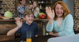 Η οικογένεια κάνει την τηλεοπτική κλήση χρησιμοποιώντας το lap-top siiting στον πίνακα στους ευτυχείς γονείς και τα παιδιά κουζιν απόθεμα βίντεο