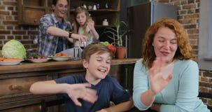 Η οικογένεια κάνει την τηλεοπτική κλήση χρησιμοποιώντας το lap-top μαγειρεύοντας τα τρόφιμα στους ευτυχείς γονείς και τα παιδιά κ φιλμ μικρού μήκους