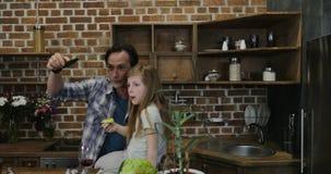 Η οικογένεια κάνει την τηλεοπτική κλήση χρησιμοποιώντας το lap-top μαγειρεύοντας τα τρόφιμα στους ευτυχείς γονείς και τα παιδιά κ απόθεμα βίντεο