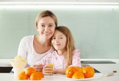 Η οικογένεια κάνει το χυμό από πορτοκάλι σε ένα juicer Στοκ φωτογραφίες με δικαίωμα ελεύθερης χρήσης